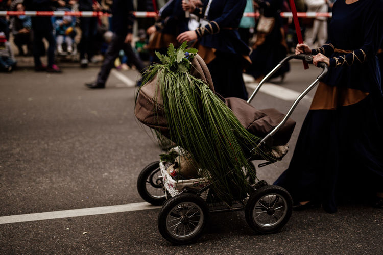 Low section of woman with baby carriage walking on street