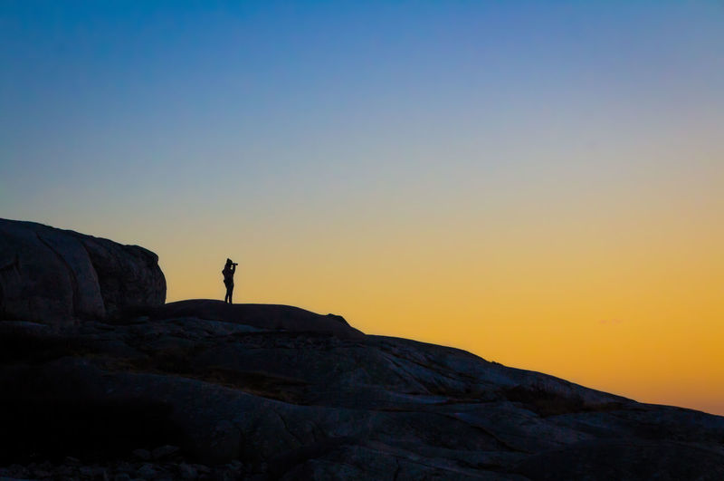 Silhouette man standing on cliff against clear sky