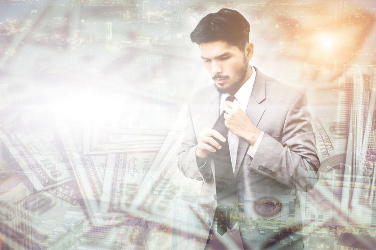 Digital composite image of businessman surrounded with paper currencies