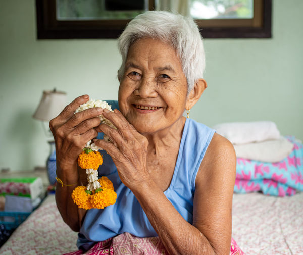 A close-up portrait of an old woman smiling and holding a flower garland. real bodies concept.