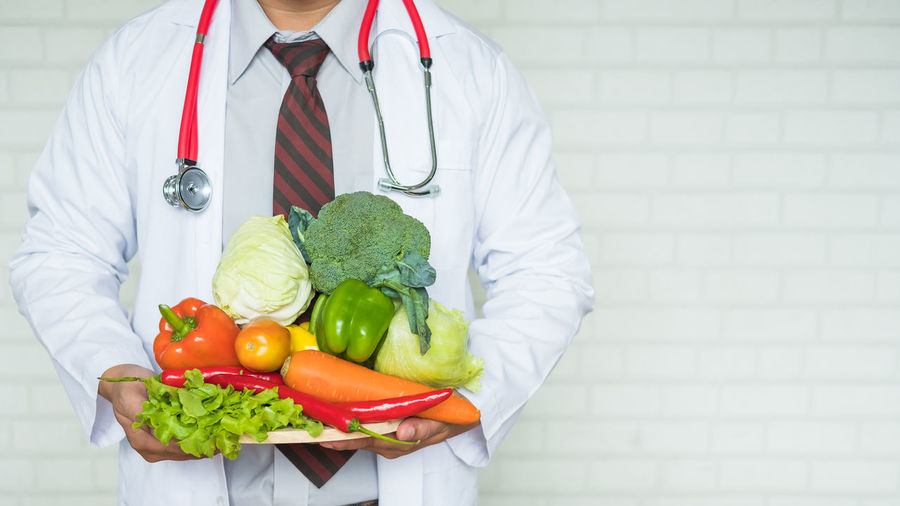 Midsection of doctor holding vegetables