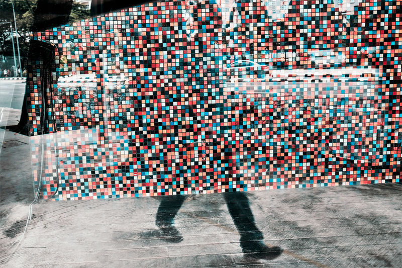 Double exposure of mosaic wall and low section of man walking on street