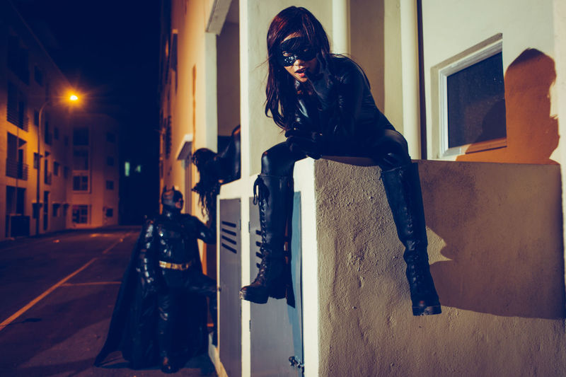Portrait of young woman wearing superhero costume sitting against building at night