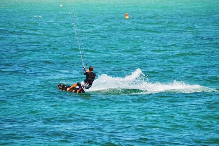Man kitesurfing in sea