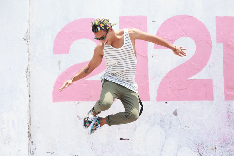 Happy Young Man Jumping Against Wall
