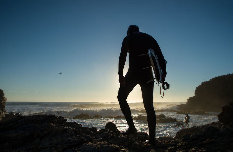 Silhouette man on rock at beach against clear blue sky