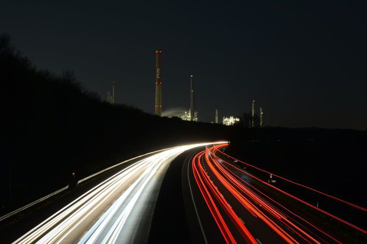 Light trails on street by smoke stacks against clear sky at night