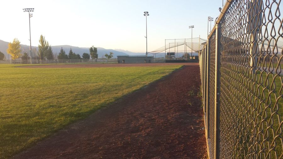 Baseball Baseball Field Beauty In Nature Chainlink Fence Day Diminishing Perspective Empty Fence Field Grass Grassy Green Color Growth Landscape Metal Nature No People Outdoors Plant Rural Scene Scenics Sky The Way Forward Tranquil Scene Tranquility