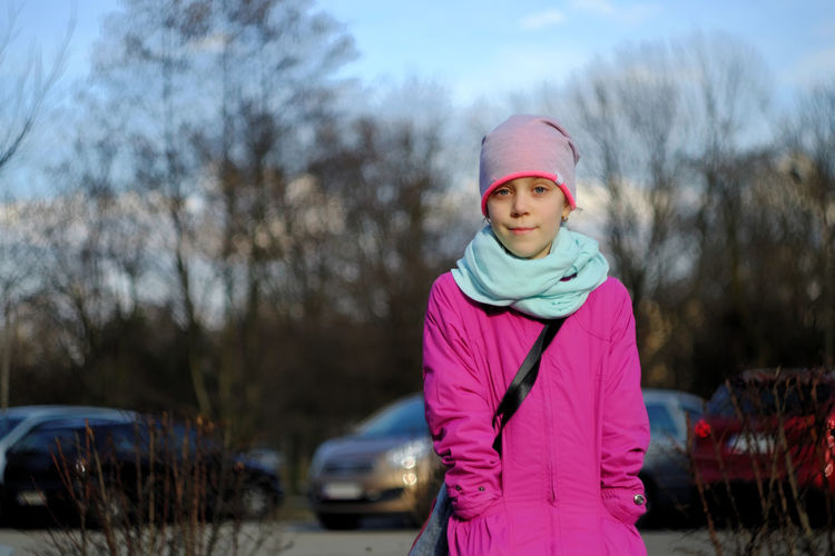 Portrait of girl wearing knit hat against cars