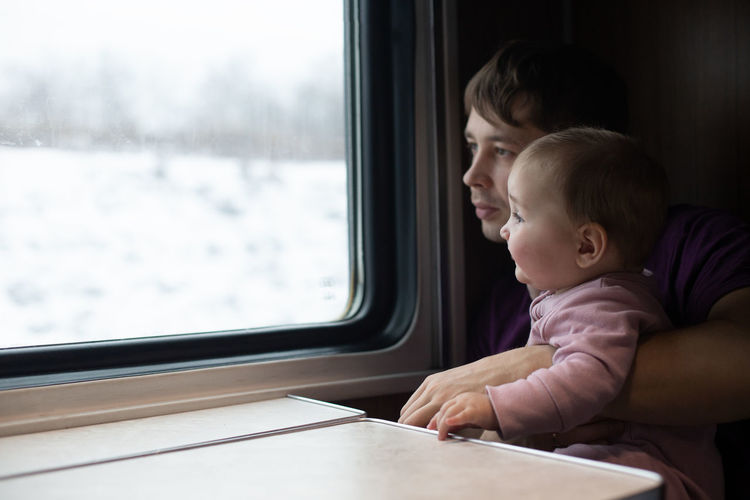 Rear view of boy looking through train window