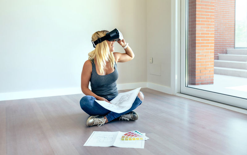 Woman wearing virtual reality simulator while sitting at home