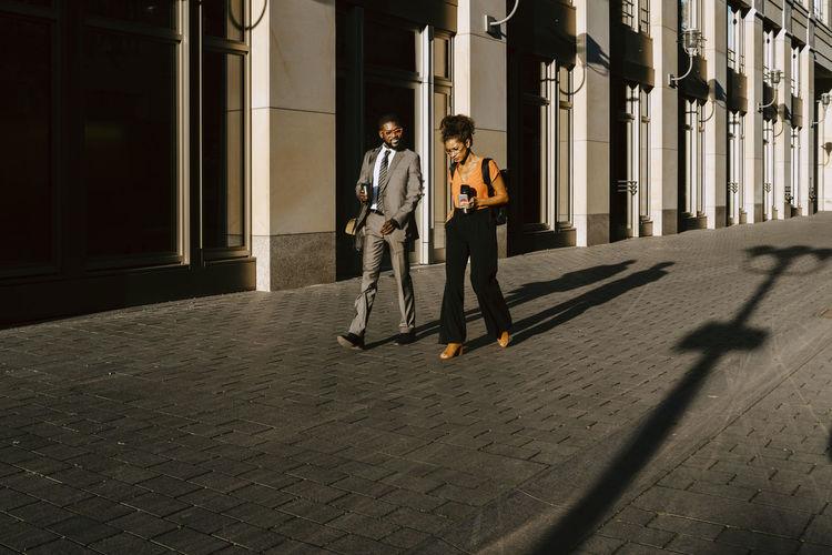 Full length of friends walking on street in city