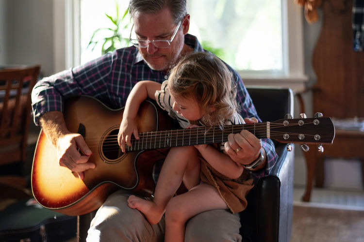 Grandfather playing guitar with granddaughter at home