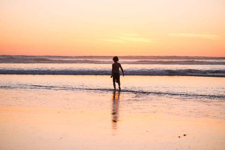 Rear view of shirtless boy walking at beach against sky during sunset