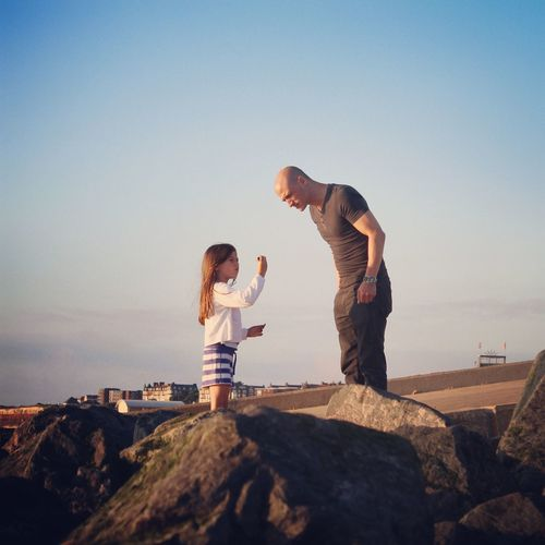 Father with daughter standing on rocks against clear sky