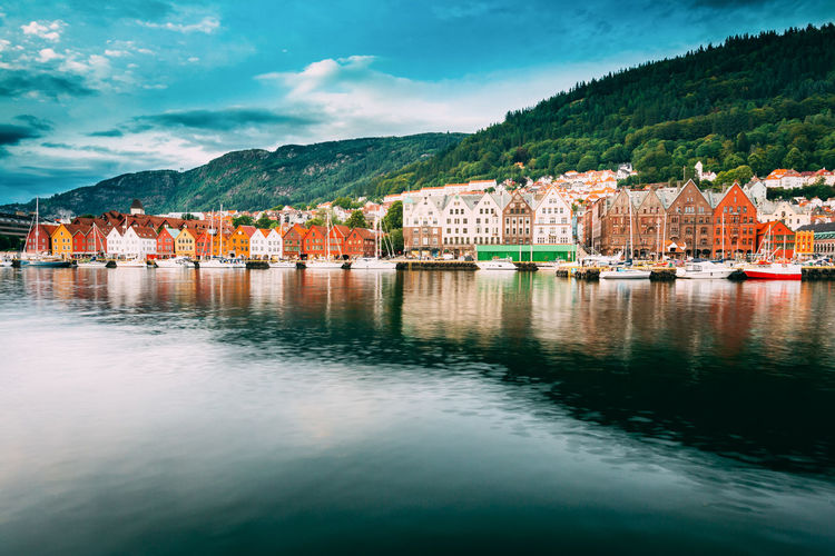 Bergen, Norway. View Of Historical Buildings Houses In Bryggen - Hanseatic Wharf In Bergen, Norway. UNESCO World Heritage Site. Famous Landmark. Destination Scenic Architecture Bergen City Cityscape Famous Norway Reflection Scandinavia Travel Boat Buiding Destination Europe Fjord House Lake Landscape Mountain Nobody Outdoor Summer Tourism Town Urban Yacht My Best Travel Photo