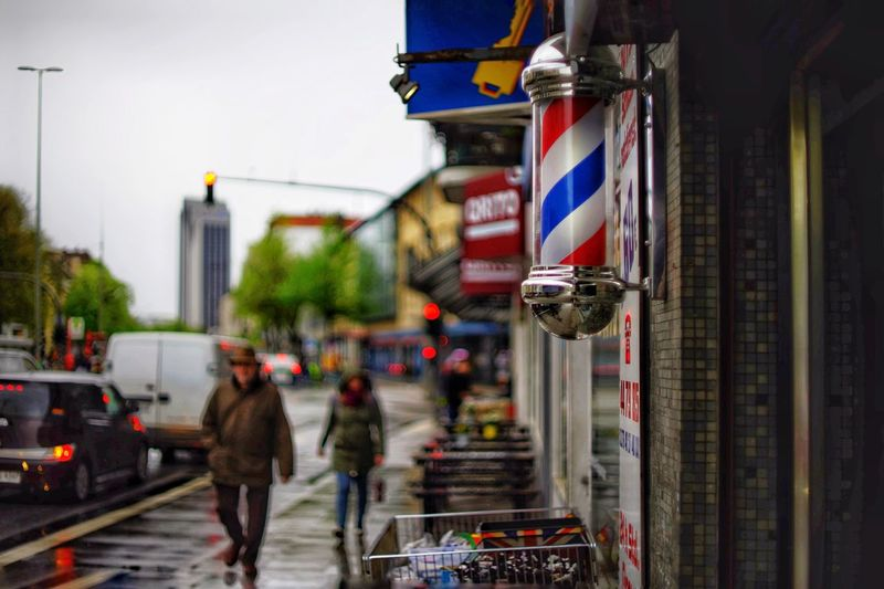 Rainy Days Small Shops Shopping Street Focus On Foreground Rainy Day Wet Street City Building Exterior Architecture Flag Built Structure Street Real People Day Men Walking Lifestyles Incidental People People Transportation Building Independence Adult Women Group Of People The Street Photographer - 2018 EyeEm Awards
