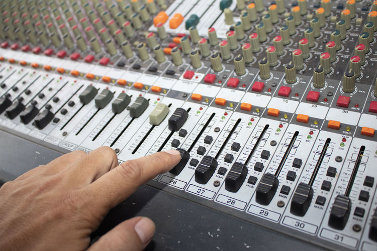 Cropped hand of man using sound mixer