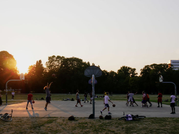 URBANANA #urbanana: The Urban Playground Available Light Clear Sky Crowd Group Group Of People Large Group Of People Leisure Activity Lifestyles Men Nature Outdoors Plant Playing Real People Skill  Sky Sport Streetphotography Sunset Team Sport Togetherness Tree