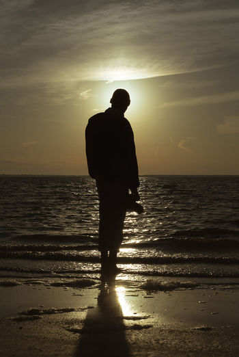 Beach Beauty In Nature Horizon Horizon Over Water Land Leisure Activity Lifestyles Men Nature One Person Real People Scenics - Nature Sea Silhouette Sky Standing Sun Sunlight Sunset Water