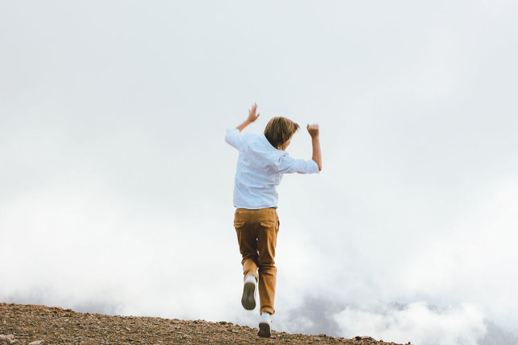 Rear view of boy jumping against sky