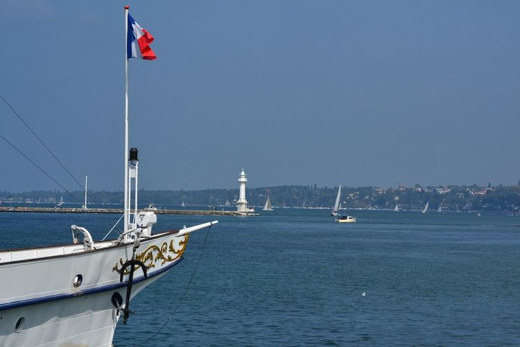 French flag on boat at sea against sky