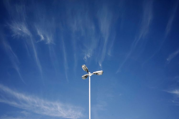 Low Angle View Sky Floodlight Blue Cloud - Sky Nature Lighting Equipment No People Day Outdoors Tall - High Street Light Beauty In Nature Motion Technology Street Sunlight Pole