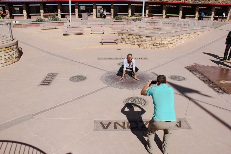 High angle view of man photographing woman at historical building on sunny day