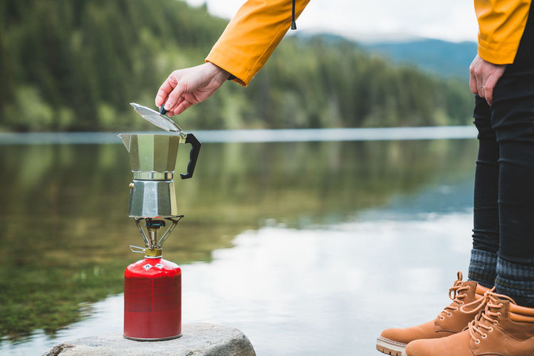 Low section of person making coffee against lake