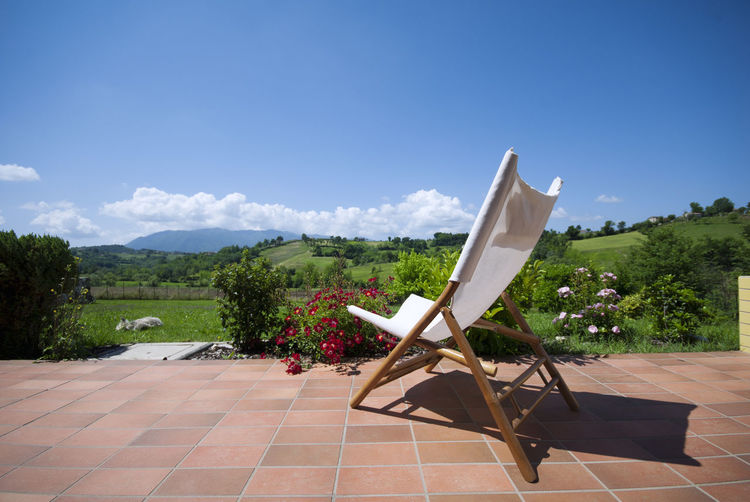 Deck Chair Against Green Landscape Against Blue Sky On Sunny Day