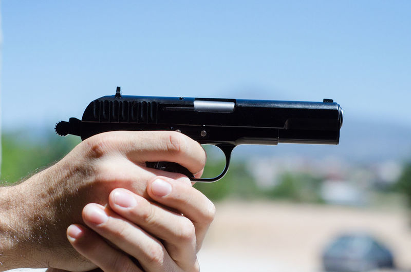Cropped Hands Holding Gun Against Clear Sky