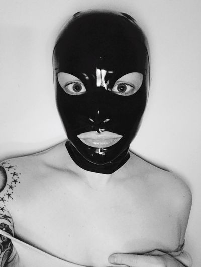 Portrait of young woman wearing mask against white background