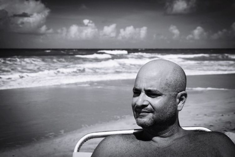 Thoughtful man looking away while sitting at beach against sky