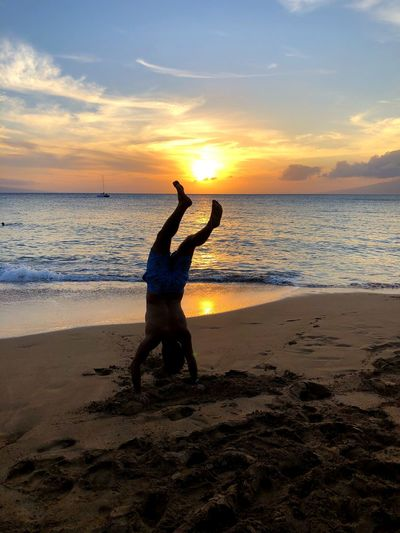 Silhouette man doing handstand at beach during sunset