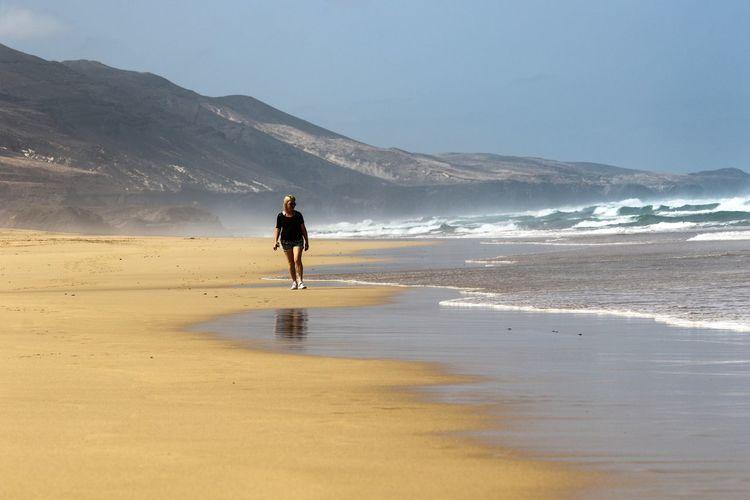 Woman walking on beach against sky
