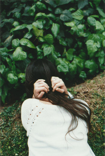 Rear view of woman bending against plants