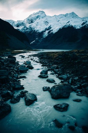 Scenic view of stream and snowcapped mountains against sky