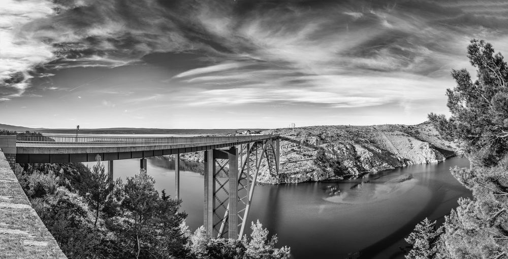 A BRIDGE ACROSS THE WATER Black & White Photography Croatia, Vinodols Fine Art Photograhy Single Span Bridge Sky And Clouds Blended Images Bridge - Man Made Structure Built Structure Cloud - Sky Highway New Infrastructure Outdoors Panoramic Landscape Pine Trees Reflection Scenics - Nature Sea Tranquil Scene Tranquility Transportation Travel, Rocky, Bright, Sunshine, Nature Water