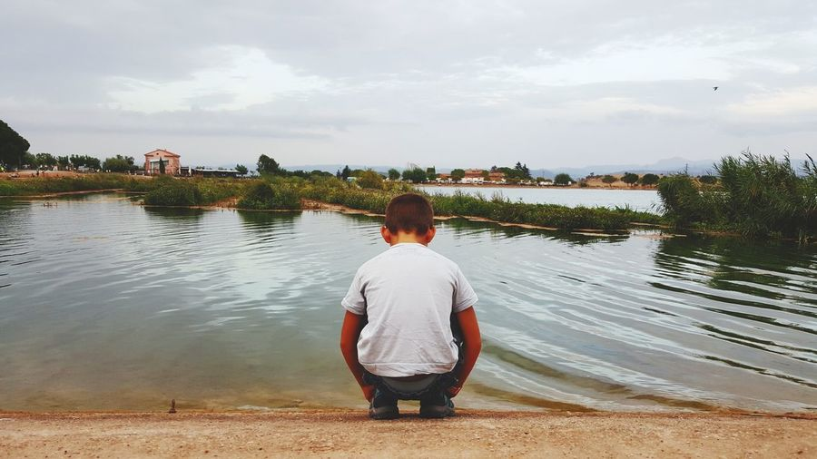 Rear View Of Boy Crouching On Riverbank Against Sky