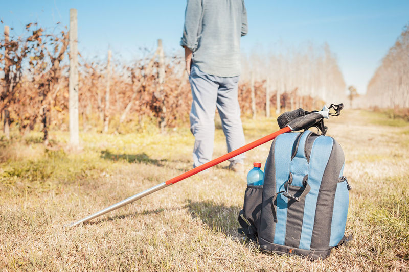 Backpack and sticks to do nordic walking on country roads. Adult Backpack Casual Clothing Day Golf Hiking Leisure Activity Men Nature Nordic Walking One Person Outdoors People Sport Sports Activity Sticks Togetherness Trekking
