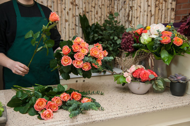 Red roses by flower pot on plant