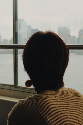 Rear View Of Woman Looking Through Window While Traveling In Ferry