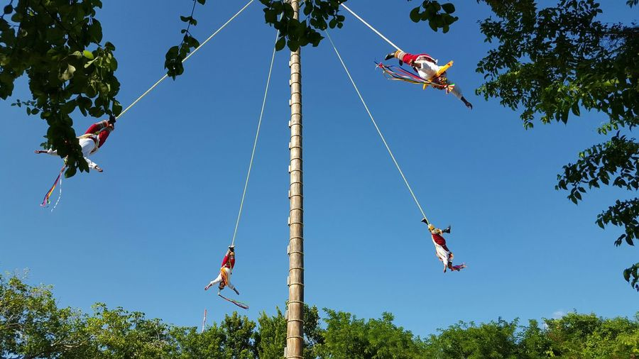 Low Angle View Of Swing Ride Against Clear Blue Sky
