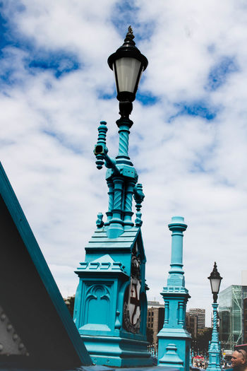 Low angle view of gas lights against cloudy sky