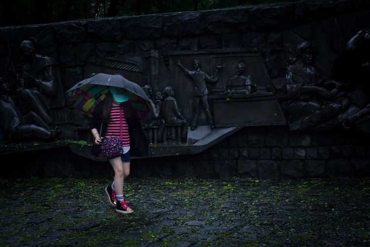Rear view of woman with umbrella standing on footpath during rainy season