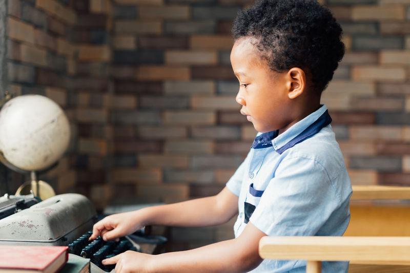 Side view of boy using typewriter