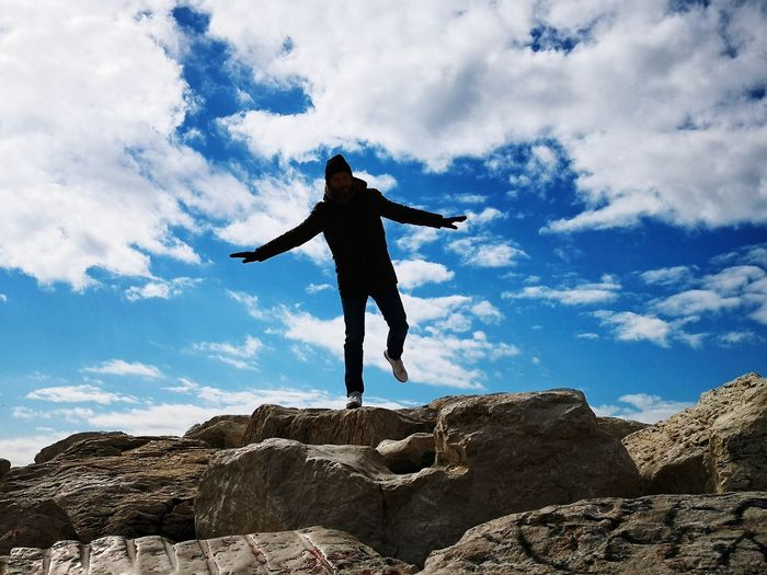 Full Length Of Man With Arms Outstretched On Rock Against Sky