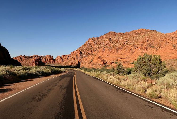 Landscape of road leading through red rock hills in Snow Canyon State Park in Utah Red Rock Utah Scenery Blue Sky Orange Color Colorful Nature Snow Canyon State Park Utah Travel Destinations EyeEm Selects Sky Road Clear Sky The Way Forward Transportation Nature Diminishing Perspective No People Scenics - Nature Copy Space Road Marking Tranquil Scene Mountain Plant Tranquility