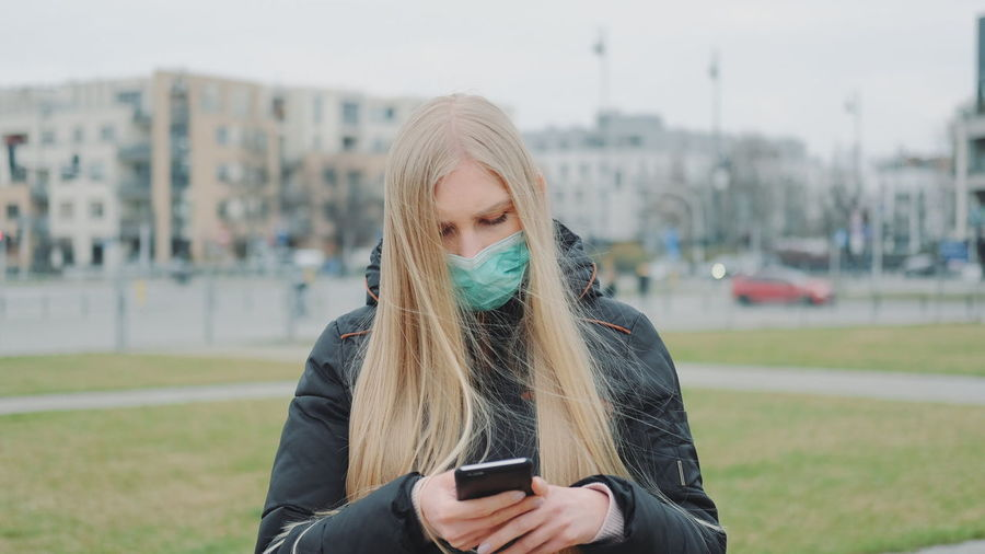Young woman wearing mask using mobile phone in city