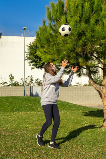 Full length of girl wearing mask playing with soccer ball in park